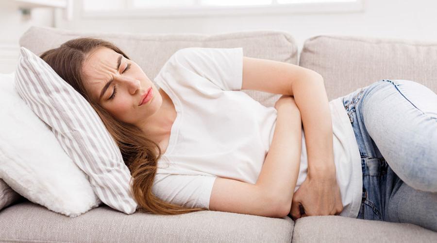 une femme tordue de douleur sur son canapé