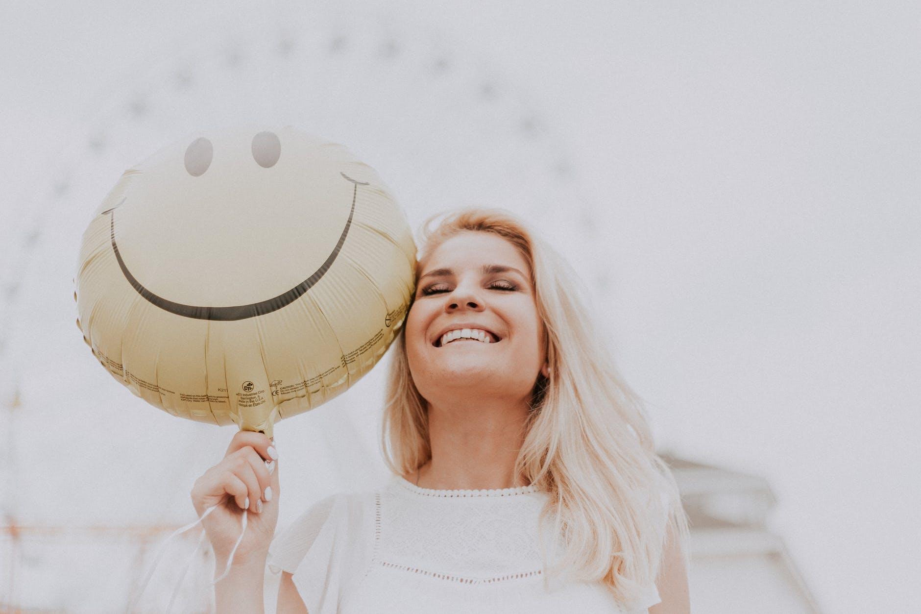 une femme souriante avec un ballon smiley