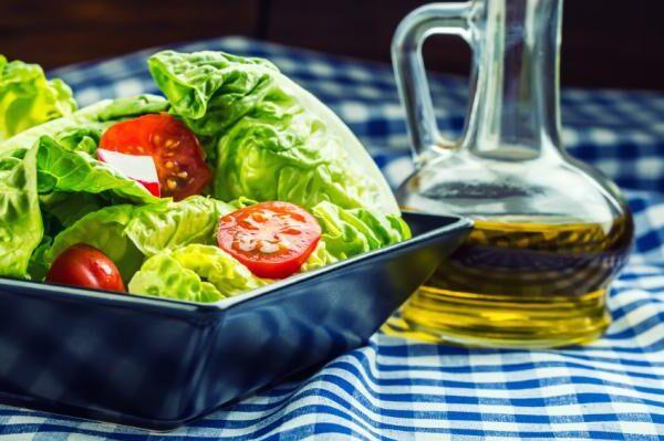 une salade a coté d'un pot d'huile d'olive