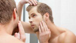 Homme examinant ses cheveux dans un miroir