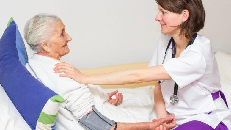 Infirmière et dame agêe dans un lit d'hôpital