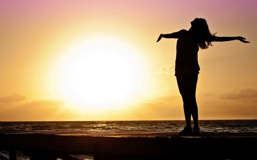 Une femme devant un coucher de soleil à la plage