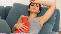 Femme avec bouillote dans son canapé