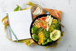 Assiette de nourriture saine à coté d'un cahier
