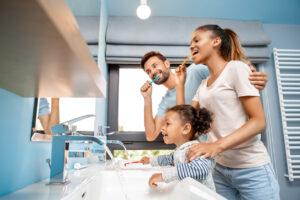 Des parents et leur fille entrain de se brosser les dents