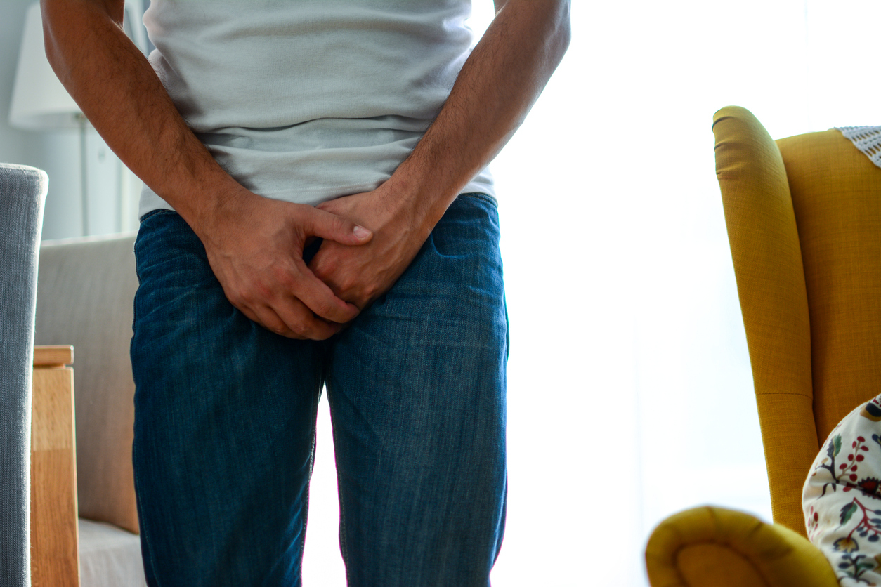 Un homme en jean avec les mains devant son pénis