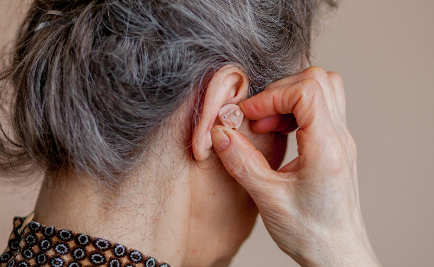 personne âgée cheveux gris met prothèse auditive oreille